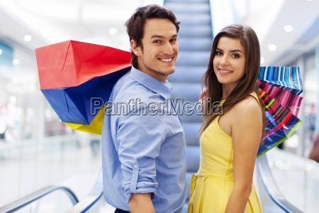 smiling couple on escalator in shopping