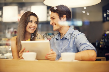 flirting couple in cafe using digital