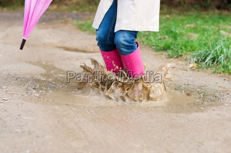 young woman with rubber boots jumping