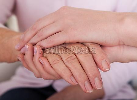 mano holding della giovane donna anziana