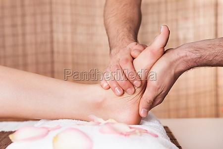 bella giovane massaggio piedi donna ottenendo