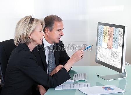 imprenditore maturo e imprenditrice guardando grafico