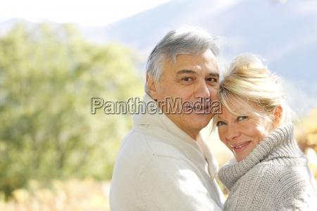 coppia senior abbracciarsi in campagna