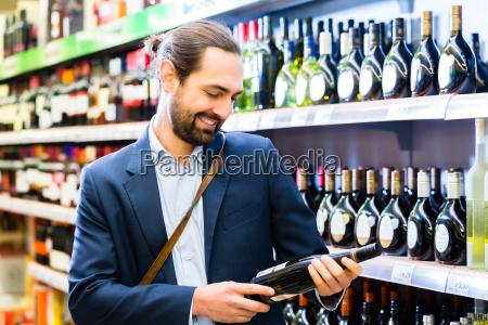 luomo sceglie il vino al supermercato