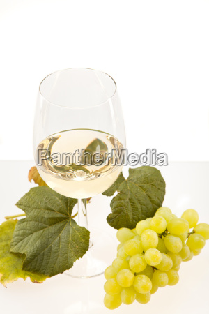 vino bianco in bicchiere con uva
