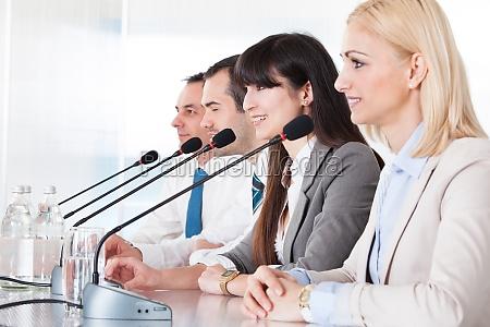 uomini daffari che parlano in microfono