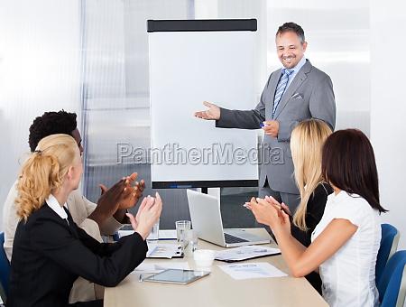 uomini daffari applaudendo per un uomo
