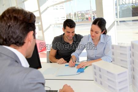 coppia in agenzia immobiliaria firma del