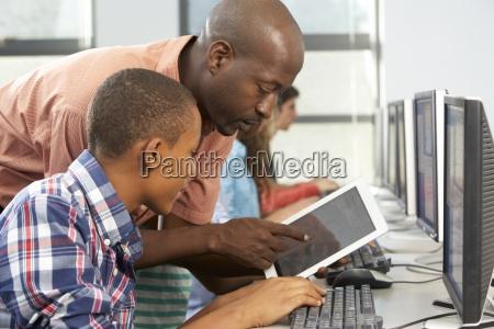 teacher helping boy to use digital