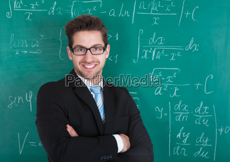 confident professor standing against blackboard