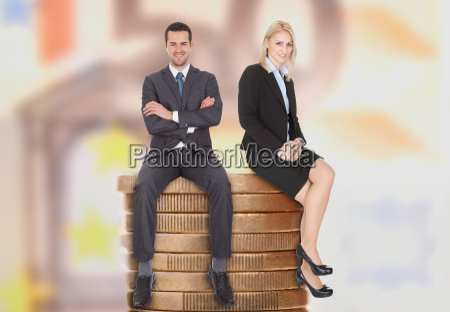 uomini daffari seduti su monete impilate