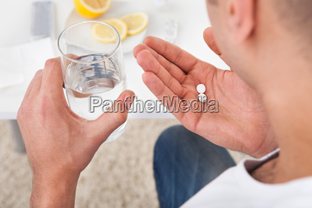 sick man taking tablets with glass