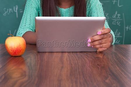 teacher holding digital tablet at school