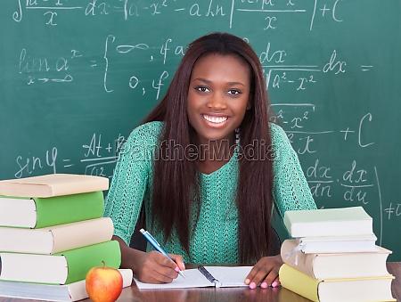 confident female teacher writing in book