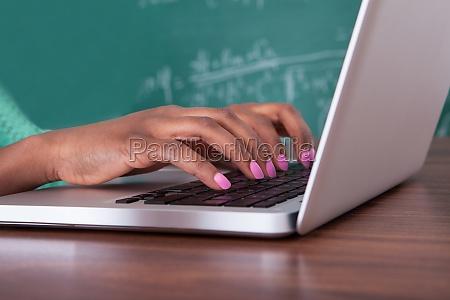teacher using laptop at desk