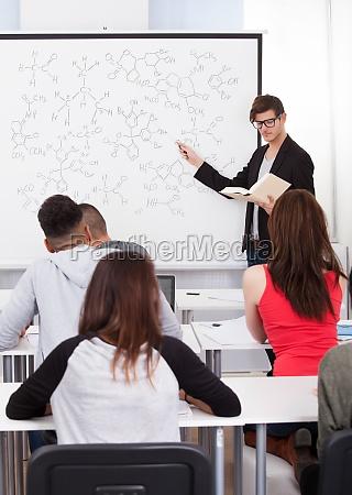 teacher teaching chemical formulas to college