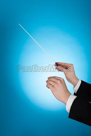 musicista tenere baton su sfondo blu