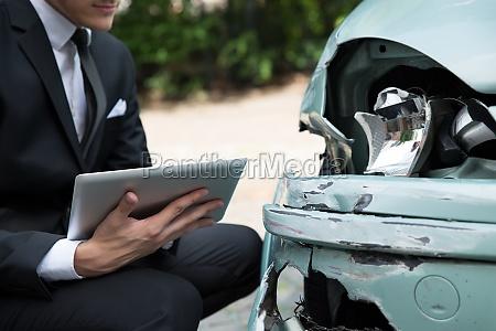 agente di assicurazione che esamina automobile