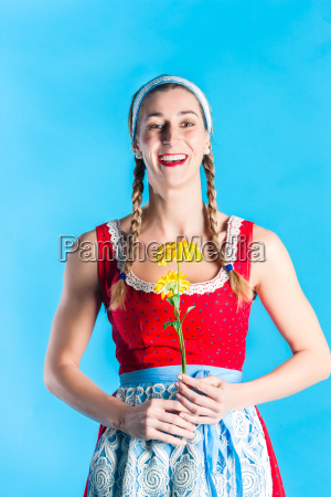 woman in dirndl dress holding flower