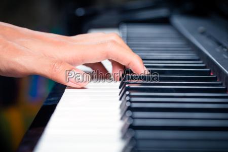 pianista asiatico maschio che suona pianoforte
