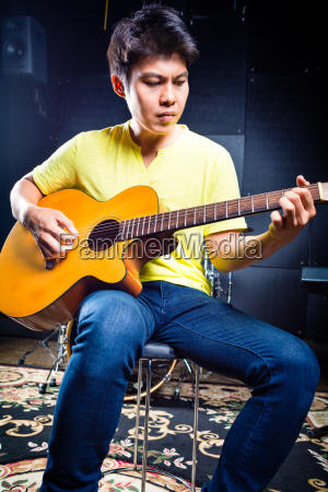 asian guitarist playing music in recording