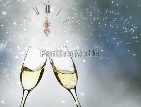 bicchieri con champagne e orologio vicino
