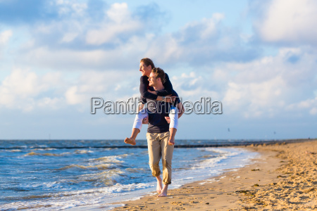 man carries piggyback woman on the