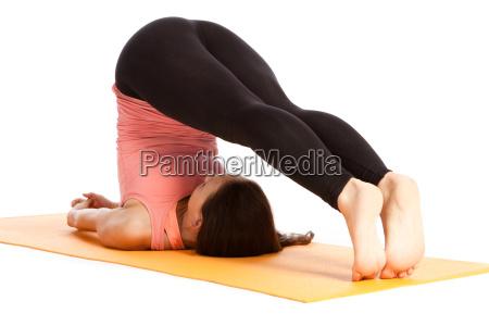 esercizio yoga sul tappeto halasana
