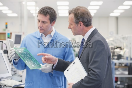 businessman and engineer examining printed circuit