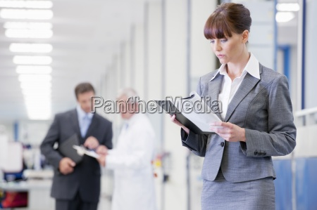 businesswoman reading paperwork in manufacturing plant