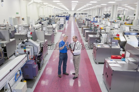 businessman and engineer inspecting part in