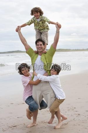 padre che porta tre figli lungo