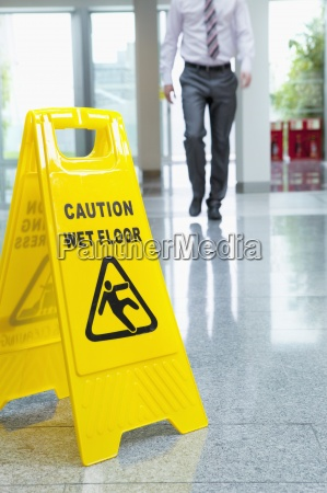 imprenditore si avvicina segno pavimento bagnato