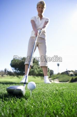 mature woman preparing to tee off