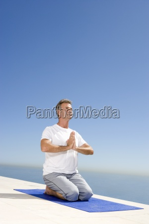 uomo maturo meditando sul tappeto di