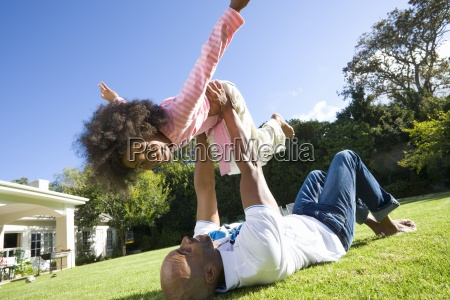 padre sdraiato sullerba sollevando la figlia