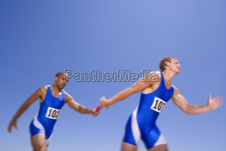 giovani atleti maschi che passano baton