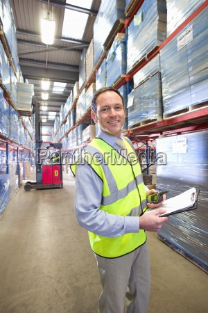 portrait of smiling warehouse manager holding