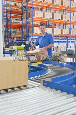 portrait of smiling worker packaging cardboard