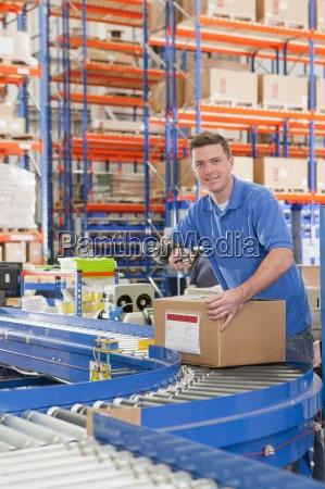 portrait of smiling worker scanning cardboard