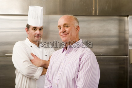 male chef and restaurant manager standing