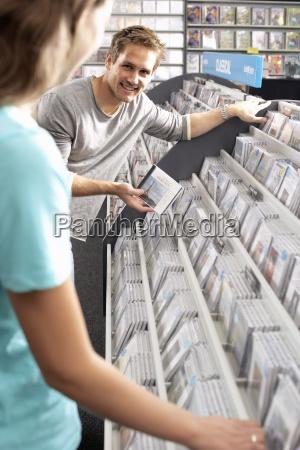 giovane uomo mostrando donna cd in