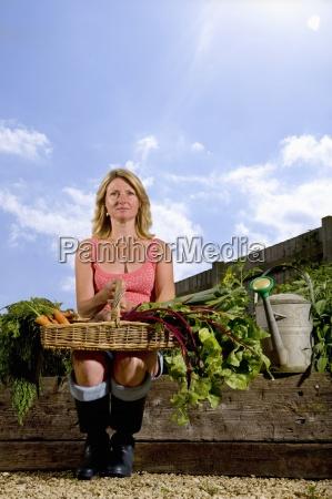 donna seduta in giardino biologico tenendo
