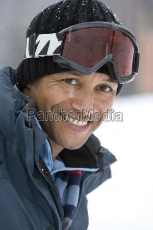 happy mature man wearing ski goggles