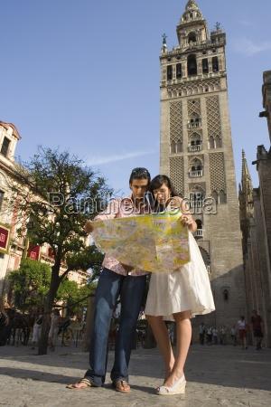 coppia giovane guardando la mappa turistica