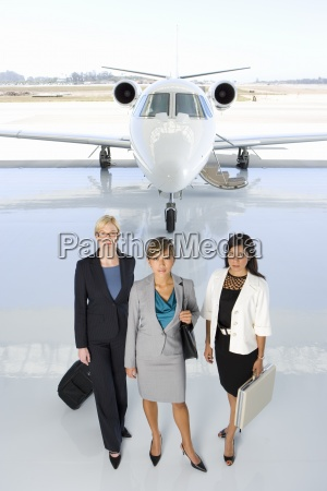 small group of women by aeroplane