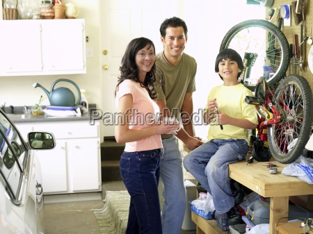 family of three fixing bicycle in