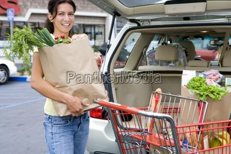 donna che carica auto con sacchetti