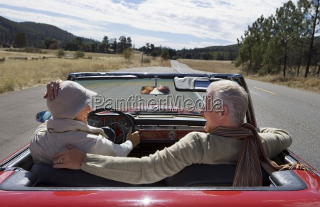 mature couple sitting in red convertible