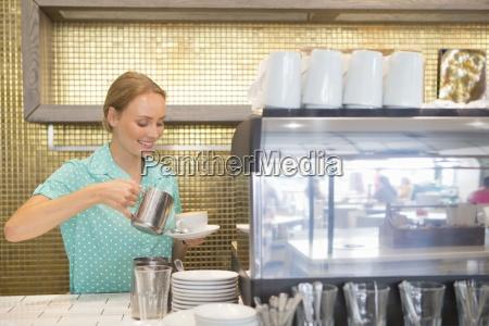 sorridente cameriera versando tazza di caffe